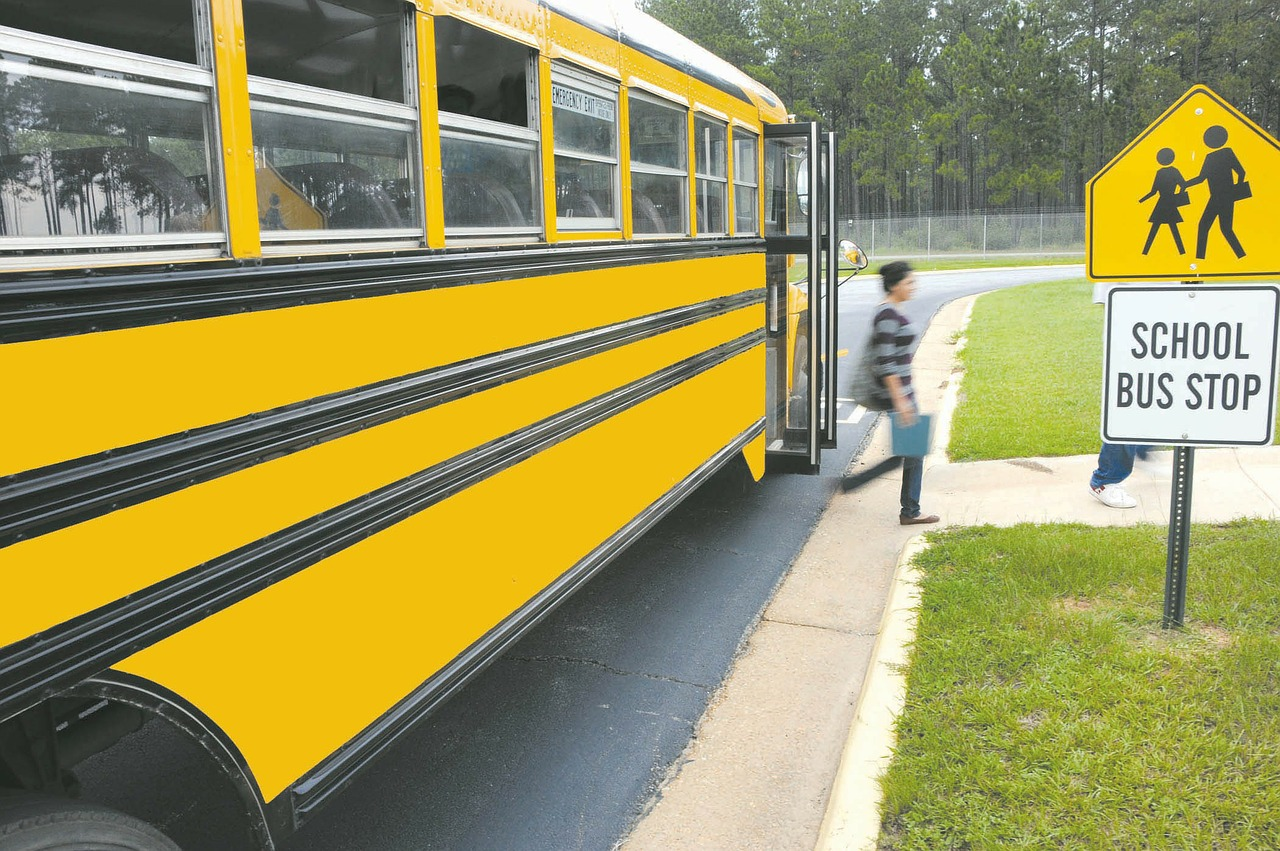 Student exiting school bus at bus stop